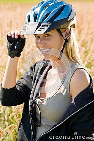 Al aire libre asoleado de la mujer joven del casco juguetón de la bici