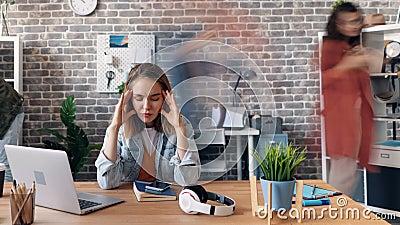 Al rallentatore dell'impiegato depresso della ragazza che sufffering dall'emicrania in ufficio video d archivio