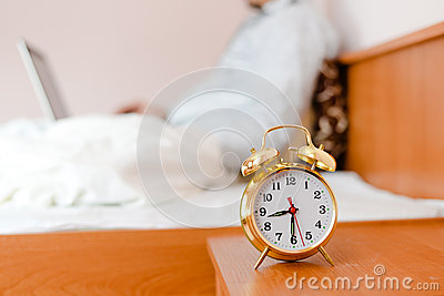 Alarm clock on foreground and business man or woman sitting in white bed working on the laptop computer on background