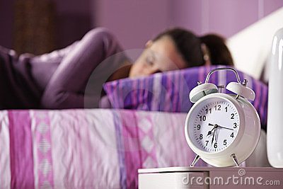 An alarm clock with a sleeping young woman