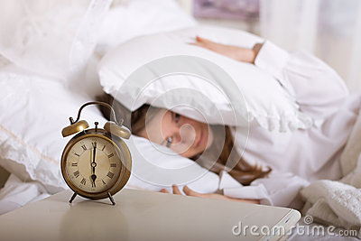 Alarm clock on table and woman sleeping