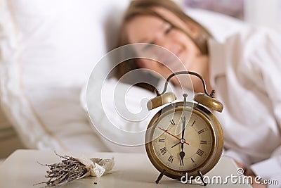 Alarm clock on table and woman sleeping