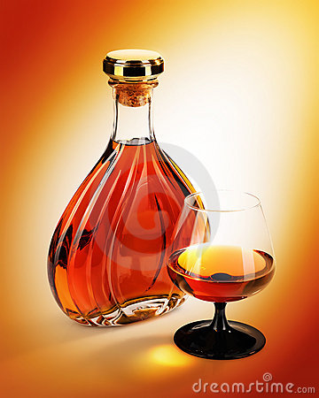 Alcohol in bottles with glass on yellow background