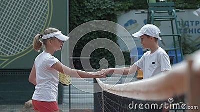 Alcohol competitivo, jugadores de tenis ambiciosos muchacho y manos de la sacudida de la muchacha mientras que se saluda cerca de metrajes