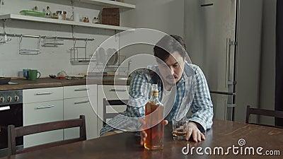 Alcool bevente dell'uomo che si siede al tavolo da cucina archivi video