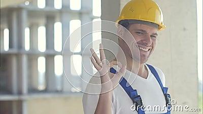 Alegre constructor mostrando el letrero correcto metrajes