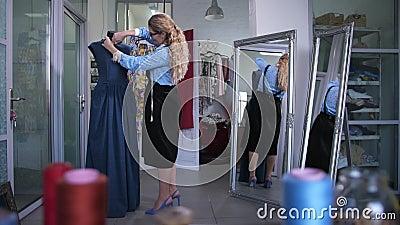 Alfaiate que faz o entalhe do decote do vestido no manequim vídeos de arquivo