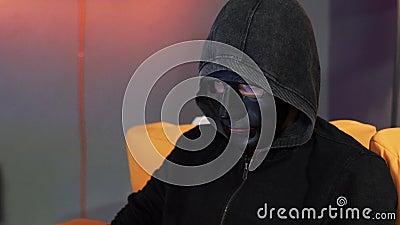 Alguém máscara protetora preta vestindo e hoody cinzento escuro senta-se no sofá alaranjado filme