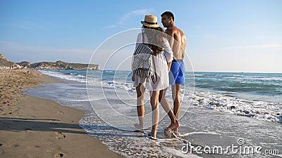 Alguns amantes caminhando na costa e segurando as mãos durante o descanso em resort O homem abraça a mulher a andar a pé na praia filme