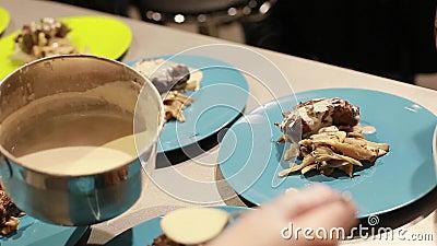 Alimento mestre da classe As mãos do cozinheiro servem o alimento nas placas, foco seletivo filme