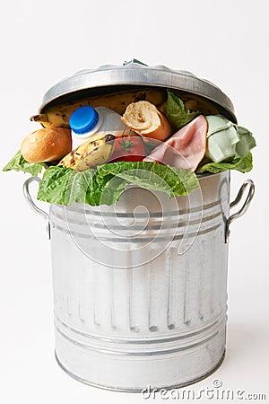 Alimentos frescos na lata de lixo para ilustrar o desperdício