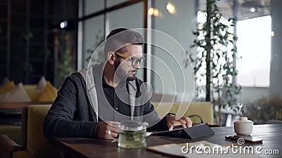 Allein steht junger Mann allein im Café in der Tageszeit, unter Verwendung der Tablette und des nippenden heißen Getränktees von  stock video