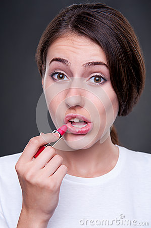 Alluring woman painting her lips