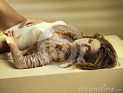 Alluring young woman lying down on the floor