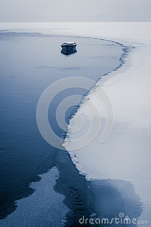 Alone boat on frozen river