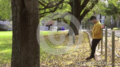 Alone men with yellow jacket using smartphone in the park of the fall. stock footage