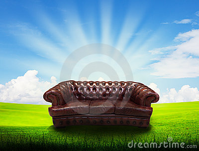 Alone sofa on grass field and blue sky