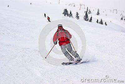 Alpen Skifahrermann, der unten gegen Höhenruder läuft