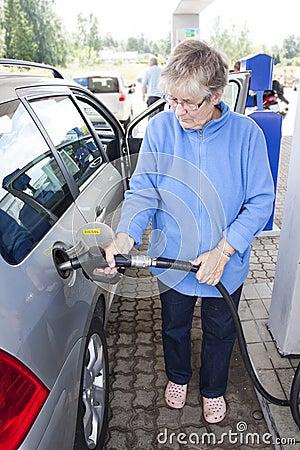 Alte Frau, die Auto tankt