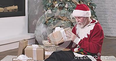 Alter kaukasischer Mann mit weißem Bart und Mosten, die Geschenkschachtel tragen und schütteln Weihnachtsmann in rotem Hut und We stock video