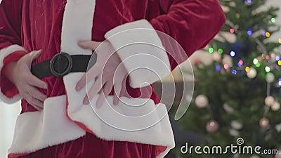 Alter kaukasischer Mann in Santa Claus-Kostüm hält seinen Bauch und tanzt vor Weihnachtsbaum Konzept des Glücks stock video