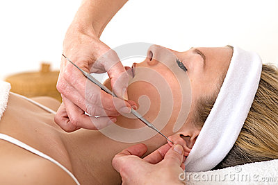 Alternative practitioner using auriculotherapy techniques.