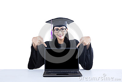 Aluno diplomado que aponta na tela vazia no portátil