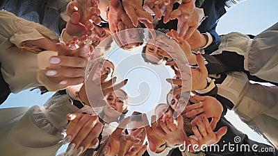 Alunos animados se juntam em um círculo em um dia ensolarado e acenam suas mãos video estoque