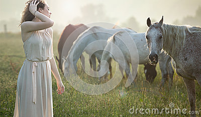 Aluring brunette walking next to the horses