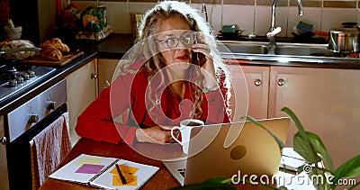 Amadureça a mulher que come o café ao falar no telefone celular na cozinha 4k vídeos de arquivo