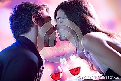 Amantes novos que beijam no restaurante, comemorando ou em d romântico