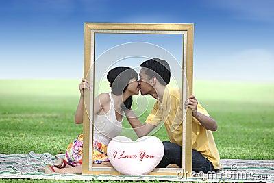 Amantes que beijam no parque