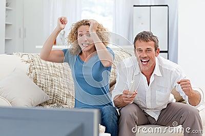 Amantes que ven la TV en la sala de estar en el país