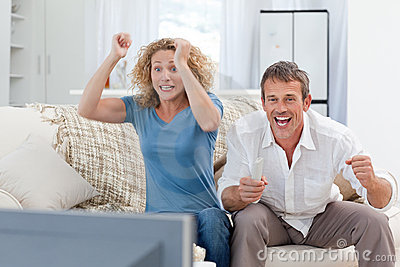 Amanti che guardano TV nel salone nel paese