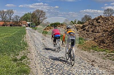 Amatörmässiga cyklister på en kullerstenväg Redaktionell Arkivbild