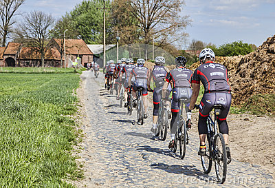 Amateur Cyclists on a Cobblestone Road Editorial Stock Photo