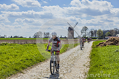 Amateur Cyclists on a Cobblestone Road Editorial Photo