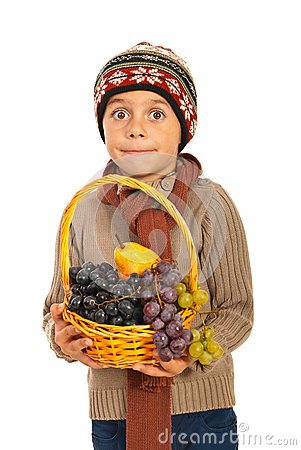 Amazed autumn boy with grapes