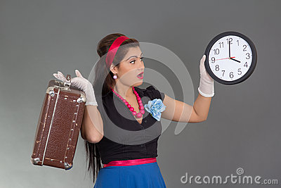 Amazed beautiful pinup woman with suitcase and clock