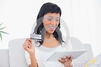 Amazed black haired woman buying online with her tablet pc