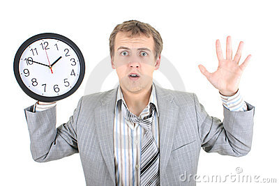 Amazed businessman in grey suit holding a clock