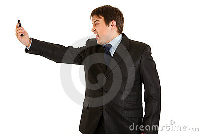 Amazed businessman yelling on mobile phone
