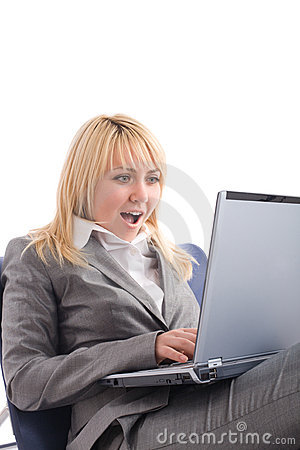Amazed businesswoman with laptop in chair
