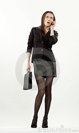 Amazed businesswoman with mobile phone