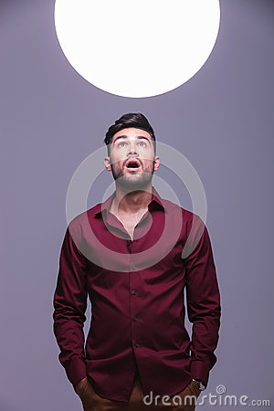 Amazed casual man  looking into a sphere of light