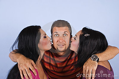 Amazed happy man with kissing women
