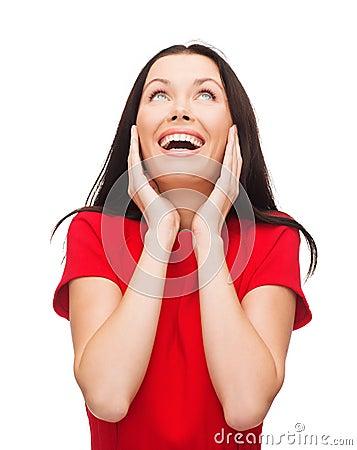 Amazed junge Frau im roten Kleid lachend