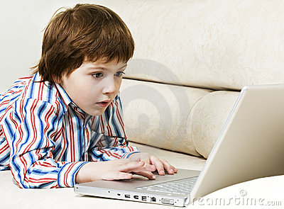 Amazed little boy with laptop