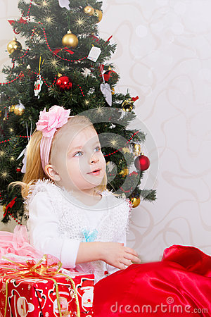 Amazed little girl under Christmas tree
