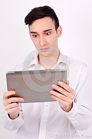 Amazed man reading from a tablet.